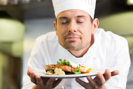 eye's closed: Closeup of a male chef with eyes closed smelling food in the kitchen