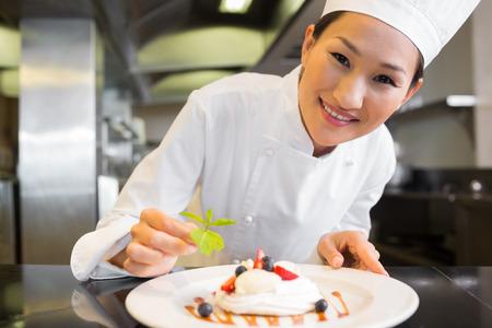 garnishing: Closeup of a smiling female chef garnishing food in the kitchen Stock Photo