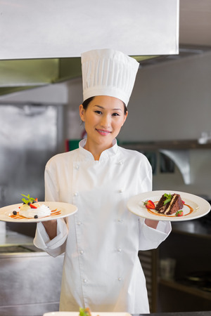 female chef: Portrait of a confident female chef holding cooked food in the kitchen Stock Photo