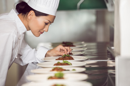Vista lateral de una mujer chef concentrada adornar los alimentos en la cocina