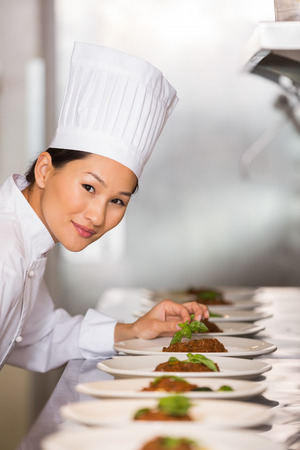 Portrait of a smiling female chef garnishing food in the kitchen