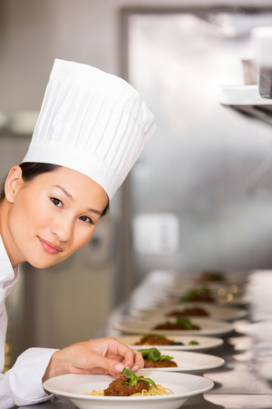 garnishing: Portrait of a smiling female chef garnishing food in the kitchen