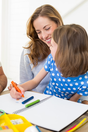 Happy mother with daughter coloring in book at home photo