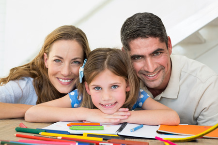 Portrait of loving family with book and crayons sitting at table photo