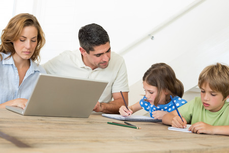Mother using laptop while father assisting children in coloring at home photo