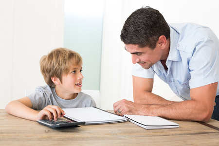 casuals: Father looking at son doing homework at home
