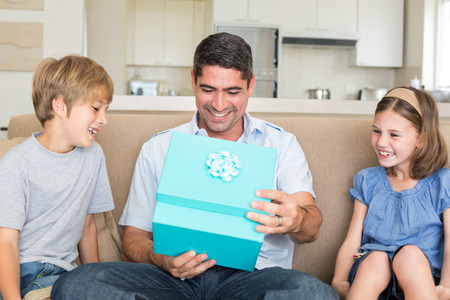 birthday present: Happy father opening gift given by children on sofa at home