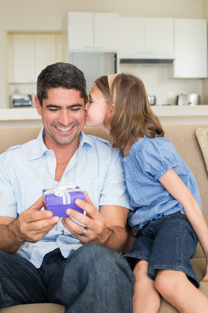 Girl kissing father holding gift box while sitting on sofa at home