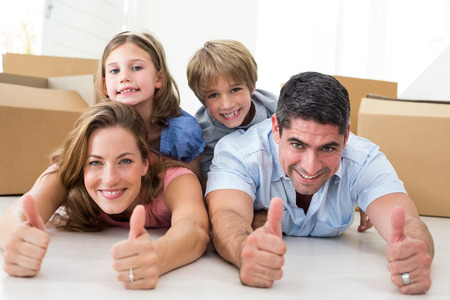Portrait of happy family showing thumbs up sign while lying in their new house photo