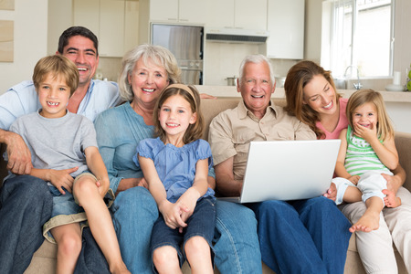 multigeneration: Portrait of cheerful multigeneration family with laptop in living room
