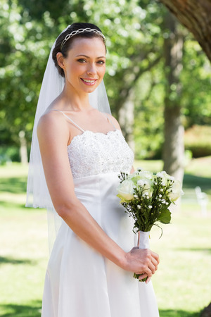 Portrait of attractive bride holding flowers in garden photo