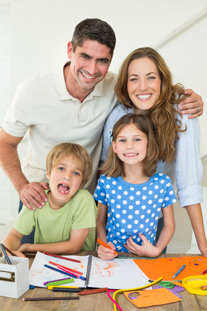 Portrait of happy parents with children drawing at table photo