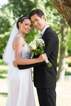 Portrait of happy newly wed couple with head to head standing in garden photo