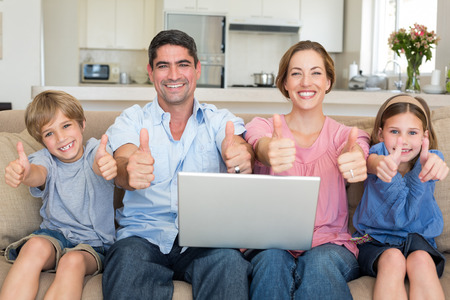 Portrait of happy family with laptop showing thumbs up sign while sitting on sofa at home photo