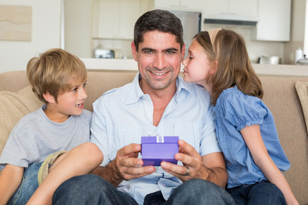 Portrait of father receiving gift from loving children in living room photo