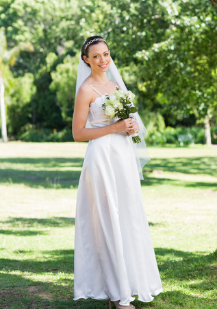 Full length portrait of bride holding flower bouquet in garden photo