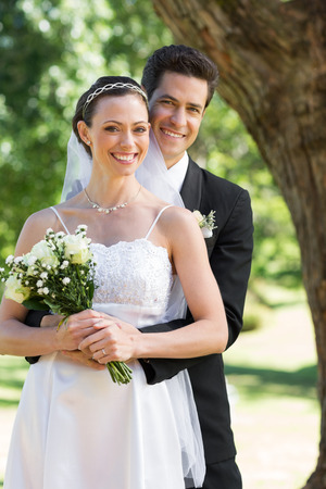 Portrait of happy groom embracing bride from behind in garden photo