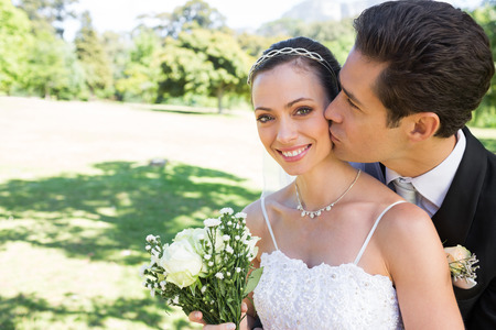 Young groom kissing beautiful bride on cheek in garden photo