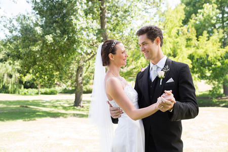 Young loving bride and groom dancing in garden photo
