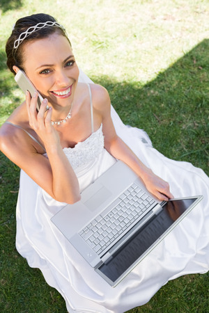 High angle portrait of happy bride with laptop using cellphone while sitting on grass in garden photo