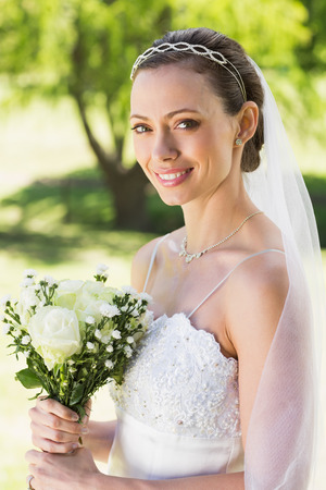 Portrait of young bride holding bouquet in garden photo