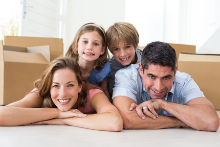 Portrait of happy family lying on floor in their new house photo