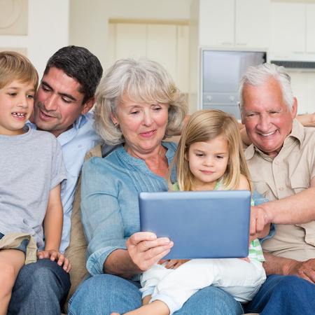 casuals: Smiling multigeneration family using digital tablet at home