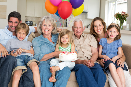 Portrait of multigeneration family celebrating girls birthday in living room photo
