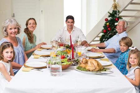 Happy multigeneration family having Christmas meal together at dining table photo
