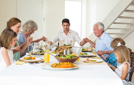 orando: Familia multigeneracional orar juntos antes de la comida en la mesa de comedor