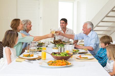 Happy multigeneration family toasting while having meal at dining table Stock Photo - 27152184