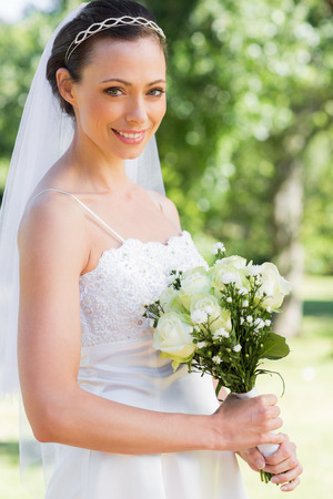 Portrait of confident bride holding flower bouquet in garden photo