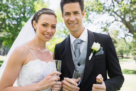 Portrait of newly wed couple holding champagne glasses in garden photo