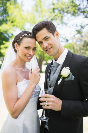 Portrait of beautiful bride and groom holding champagne flutes in park photo