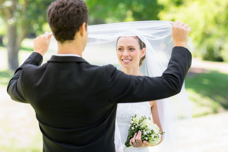 Young loving groom lifting veil of bride in park photo