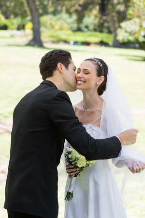 Young romantic groom kissing bride in garden photo