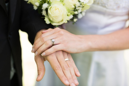 Closeup of bride and groom showing wedding rings touching hands photo