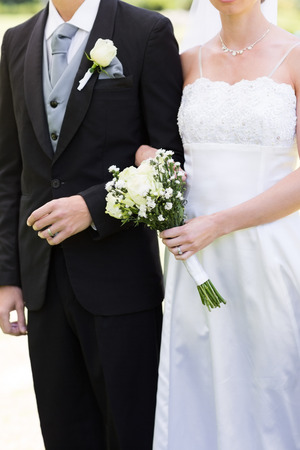 Mid section of young bride and groom holding hands in park photo