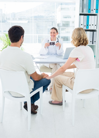 Expectant couple consulting female doctor in clinic photo
