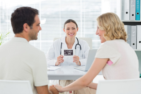 gynaecologist: Happy female gynaecologist looking at expectant couple in clinic Stock Photo