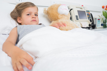 Portrait of cute girl with stuffed toy lying in hospital bed photo