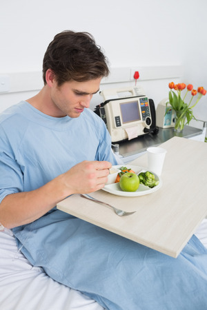 Handsome man eating healthy food in hospital ward photo