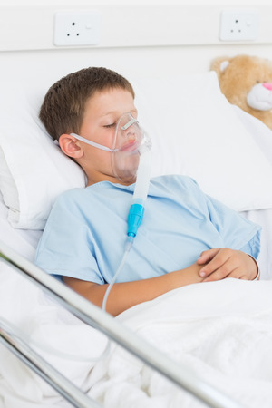 Sick little boy with oxygen mask in hospital ward photo
