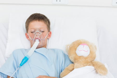 Sick boy wearing oxygen mask sleeping beside stuffed toy in hospital bed photo