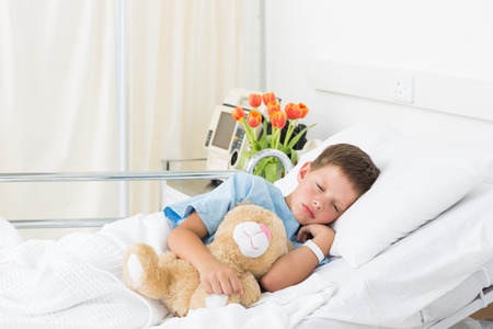 Sick little boy sleeping with teddy bear in hospital bed photo