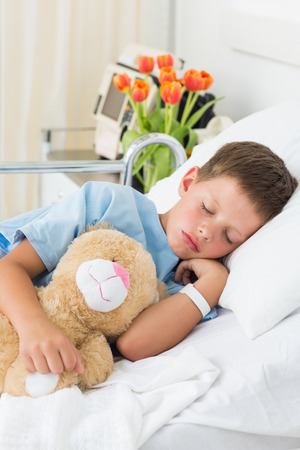 Sick little boy with teddy bear sleeping in hospital bed photo