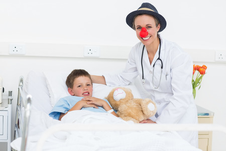 sick teddy bear: Portrait of happy female doctor in clown costume with sick boy in hospital bed Stock Photo