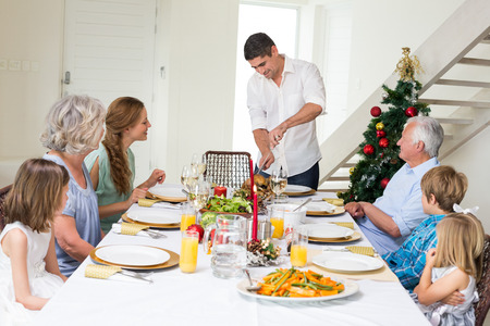 Father serving Christmas meal to family at dining table photo