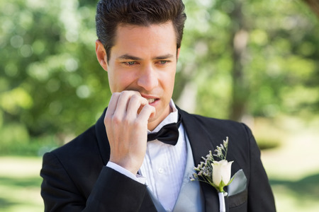 Closeup of young groom biting nails in garden photo