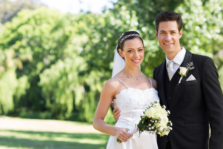 Portrait of newly wed couple smiling in garden Stock Photo